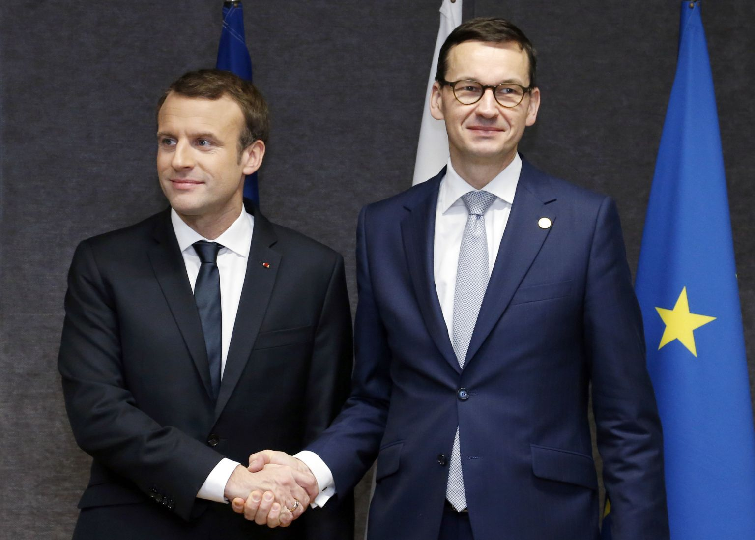 KFrench President Emmanuel Macron, left, shakes hands with Polish Prime Minister Mateusz Morawiecki prior to a meeting on the sidelines of an EU summit in Brussels on Friday, Dec. 15, 2017. EU leaders meet Friday to launch Brexit talks into a new phase and to discuss the euro and banking union. (Francois Lenoir, Pool Photo via AP)