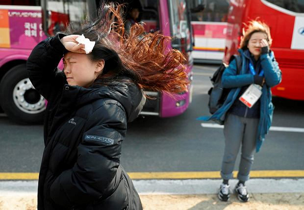People block their faces from the wind as they leave buses at the 2018 Winter Olympics in Gangneung, South Korea, Wednesday, Feb. 14, 2018. Officials are asking spectators to evacuate the Olympic Park in the coastal city of Gangneung and take shelter indoors because of strong winds.(AP Photo/John Locher) SLOWA KLUCZOWE: 2018 Pyeongchang Olympic Games;Winter Olympic games;Sports;Events;XXIII Olympiad