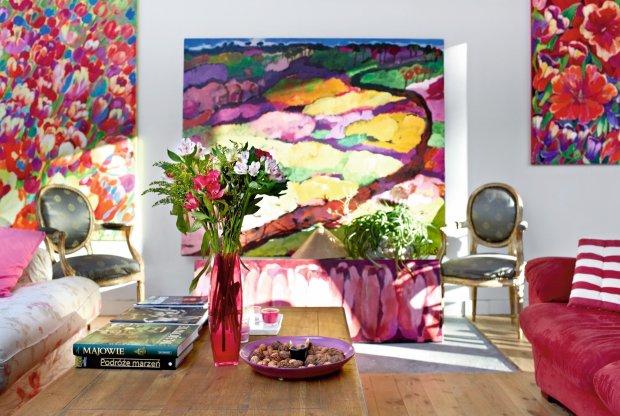 W salonie stoją stare francuskie krzesła upolowane na pchlim targu w Broniszach. Dębowa ława z Almi Decor. Piękna podłoga w salonie i pracowni z sosonowych desek lekko wybielonych i zaolejowanych. Obrazy: po lewej
