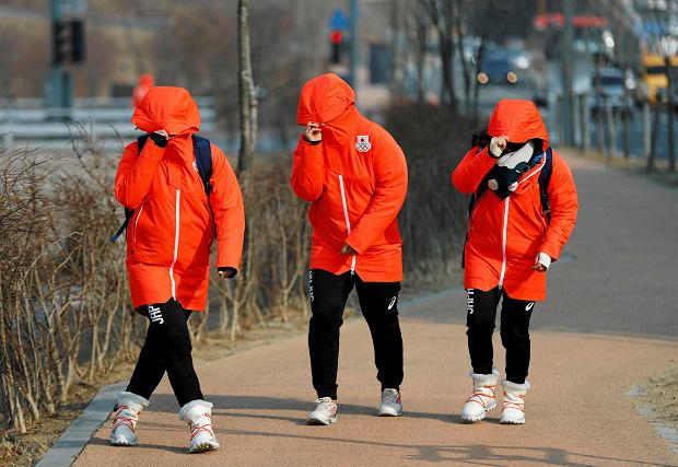 Members of the Japanese team block out wind as they walk to the Gangneung Olympic Village at the 2018 Winter Olympics in Gangneung, South Korea, Wednesday, Feb. 14, 2018. Officials are asking spectators to evacuate the Olympic Park in the coastal city of Gangneung and take shelter indoors because of strong winds. (AP Photo/John Locher) SLOWA KLUCZOWE: 2018 Pyeongchang Olympic Games;Winter Olympic games;Sports;Events;XXIII Olympiad