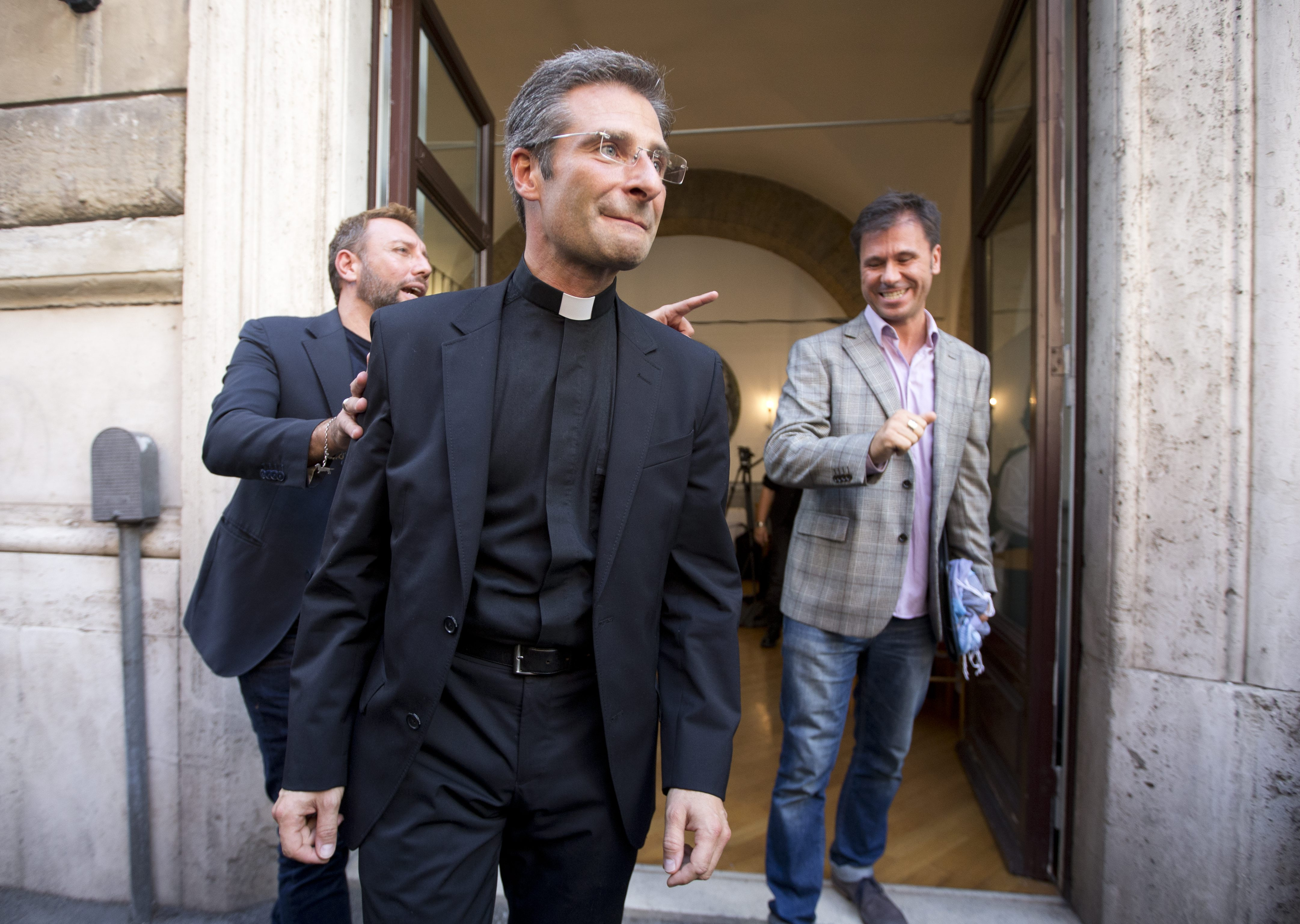 Monsignor Krzysztof Charamsa, center, and his partner Eduard, right,  surname not given, leave a restaurant after a press conference in downtown Rome, Saturday Oct. 3, 2015. Vatican on Saturday fired a monsignor who came out as gay on the eve of a big meeting of the world's bishops to discuss church outreach to gays, divorcees and more traditional Catholic families. (AP Photo/Alessandra Tarantino)