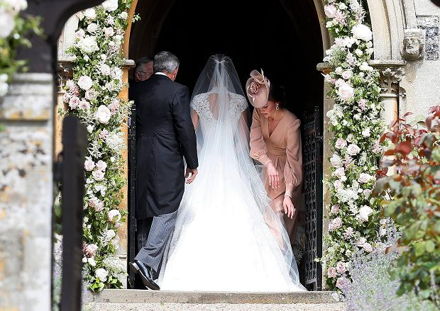 Kate, Duchess of Cambridge, right, arranges the train of her sister of her sister Pippa Middleton as she arrives with her father Michael Middleton for her wedding to James Matthews at St Mark's Church in Englefield, England Saturday, May 20, 2017. Middleton, the sister of Kate, Duchess of Cambridge is to marry hedge fund manager James Matthews in a ceremony Saturday where her niece and nephew Prince George and Princess Charlotte are in the wedding party, along with sister Kate and princes Harry and William. (AP Photo/Kirsty Wigglesworth, Pool)