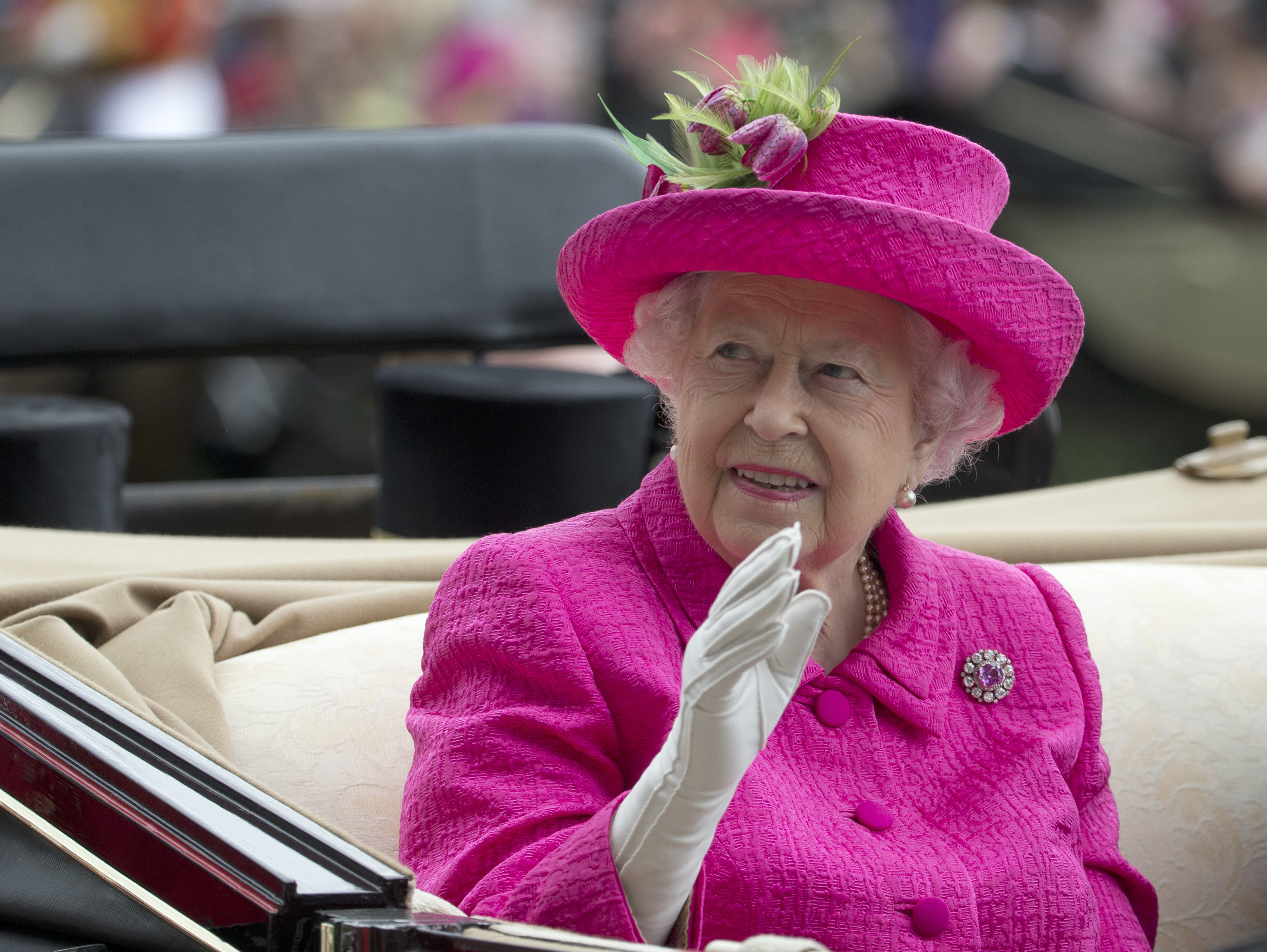 FILE - In this Thursday, June 22, 2017 file photo, Britain's Queen Elizabeth II waves to the crowd as she arrives by open carriage into the parade ring on the third day of the Royal Ascot horse race meeting, which is traditionally known as Ladies Day, in Ascot, England. Newly leaked papers have revealed that Queen Elizabeth II has placed some of her private money into offshore tax havens. According to records obtained by the International Consortium of Journalists, the queen,Äos investment managers have placed roughly 10 million pounds ($13 million) in offshore portfolios in the Cayman Islands and Bermuda. (AP Photo/Alastair Grant, File)