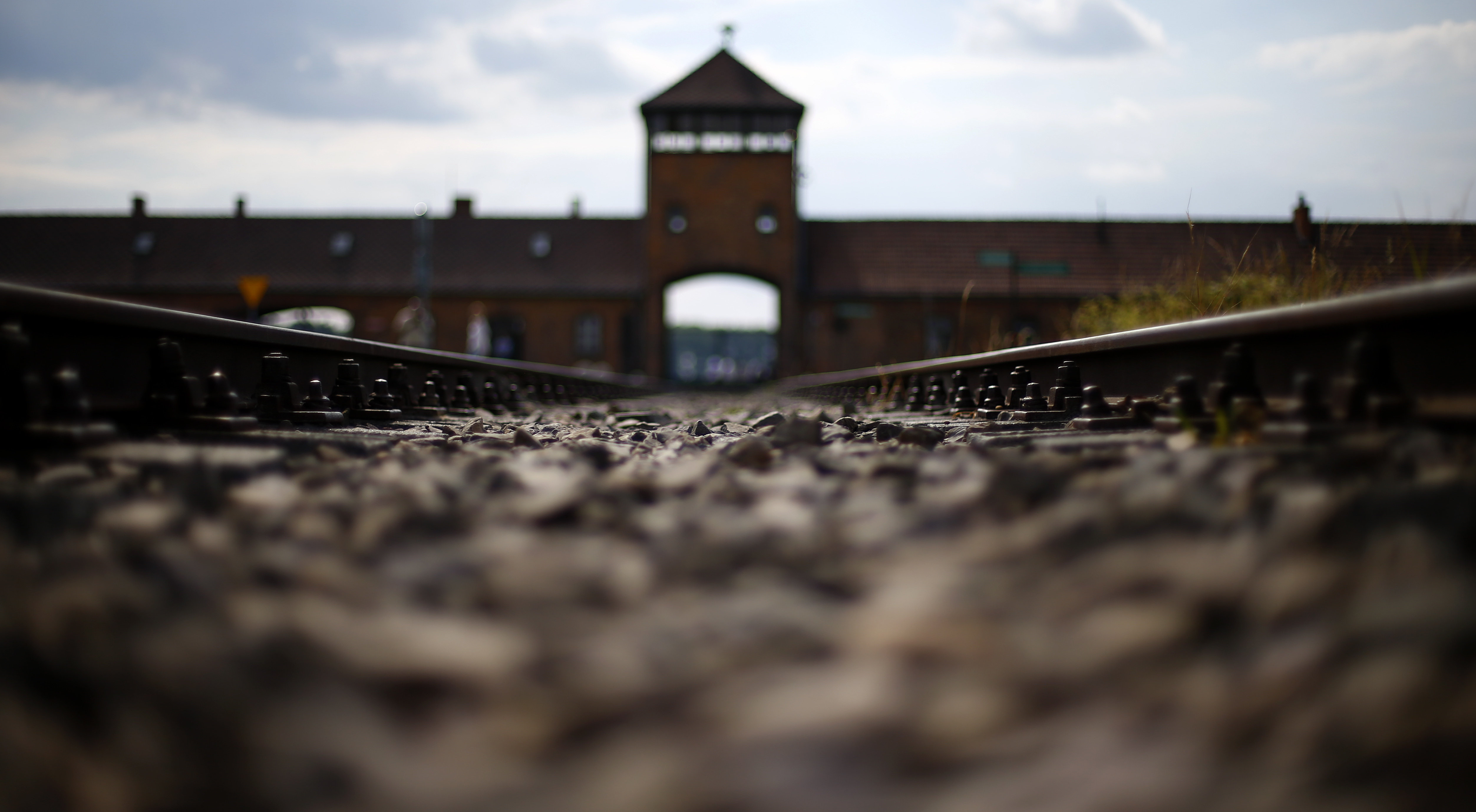 FILE - In this June 25, 2015 file photo railway tracks lie in front of the main entrance of former Auschwitz-Birkenau Nazi death camp in Oswiecim, Poland. Poland's Senate has backed legislation regulating Holocaust speech, calling for up to three years in prison for any intentional attempt to falsely attribute the crimes of Nazi Germany to the Polish state or people.  (AP Photo/Matthias Schrader, file)