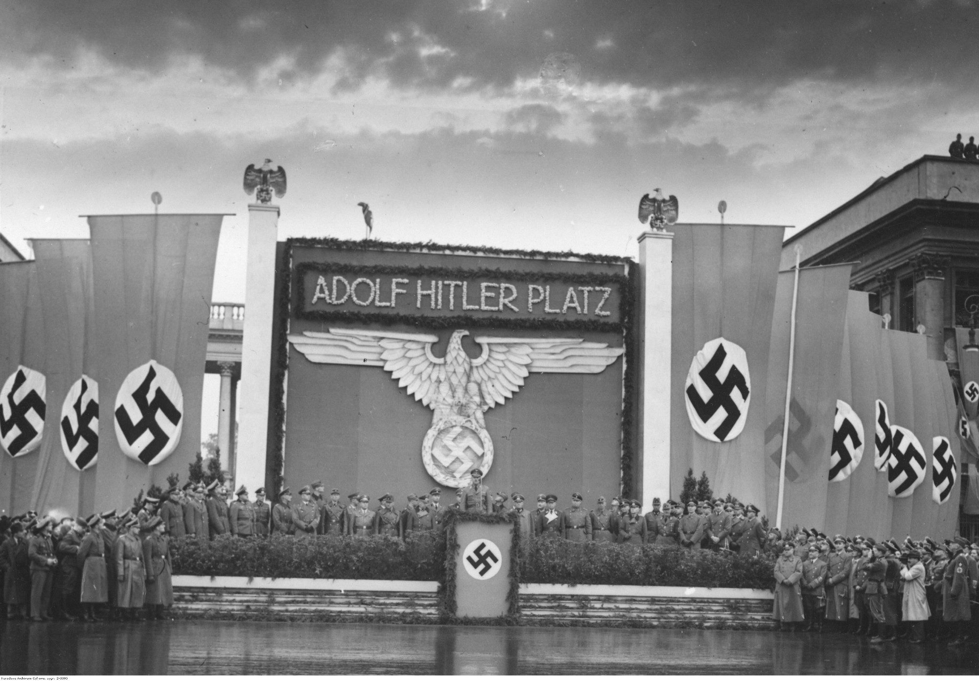 Uroczystości z okazji pierwszej rocznicy wybuchu II wojny światowej. Przemianowanie placu Saskiego na plac Adolfa Hitlera. Przemawia starosta Warszawy Ludwig Leist. Widoczna dekoracja z flagami i godłem III Rzeszy, 1 września 1940 r. (fot. Narodowe Archiwum Cyfrowe)