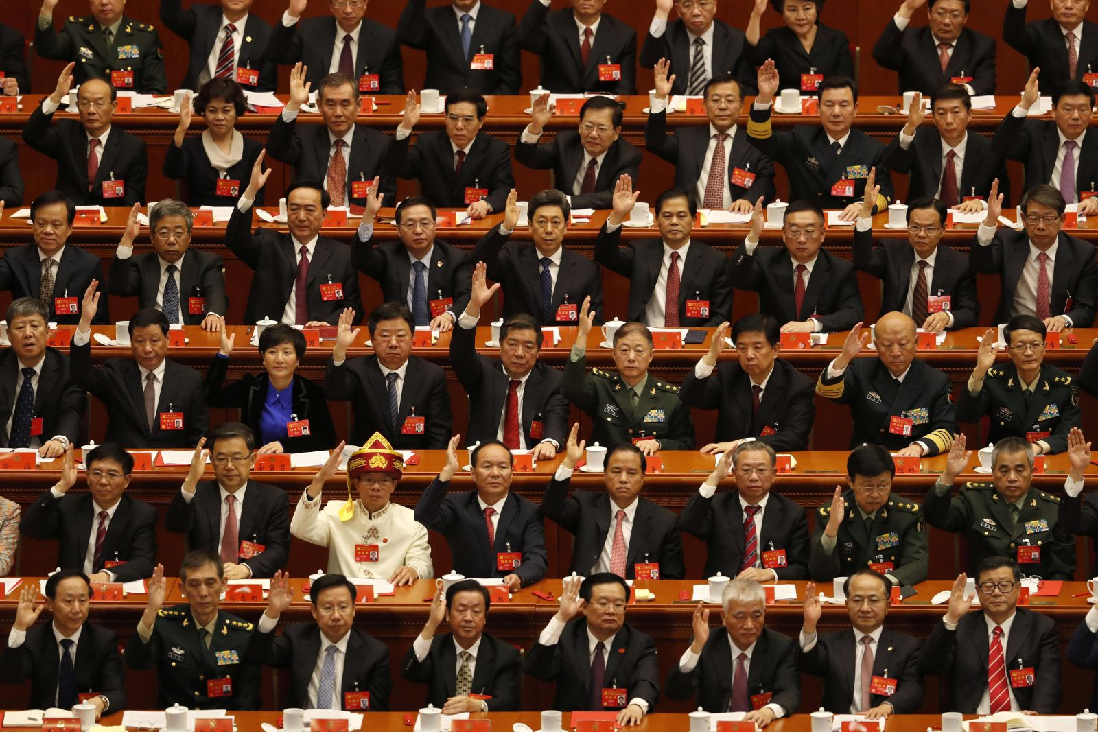 In this Tuesday, Oct. 24, 2017, file photo, delegates raise their hands to show approval of work reports during the closing ceremony for the 19th Party Congress at the Great Hall of the People in Beijing. (AP Photo/Andy Wong, File)