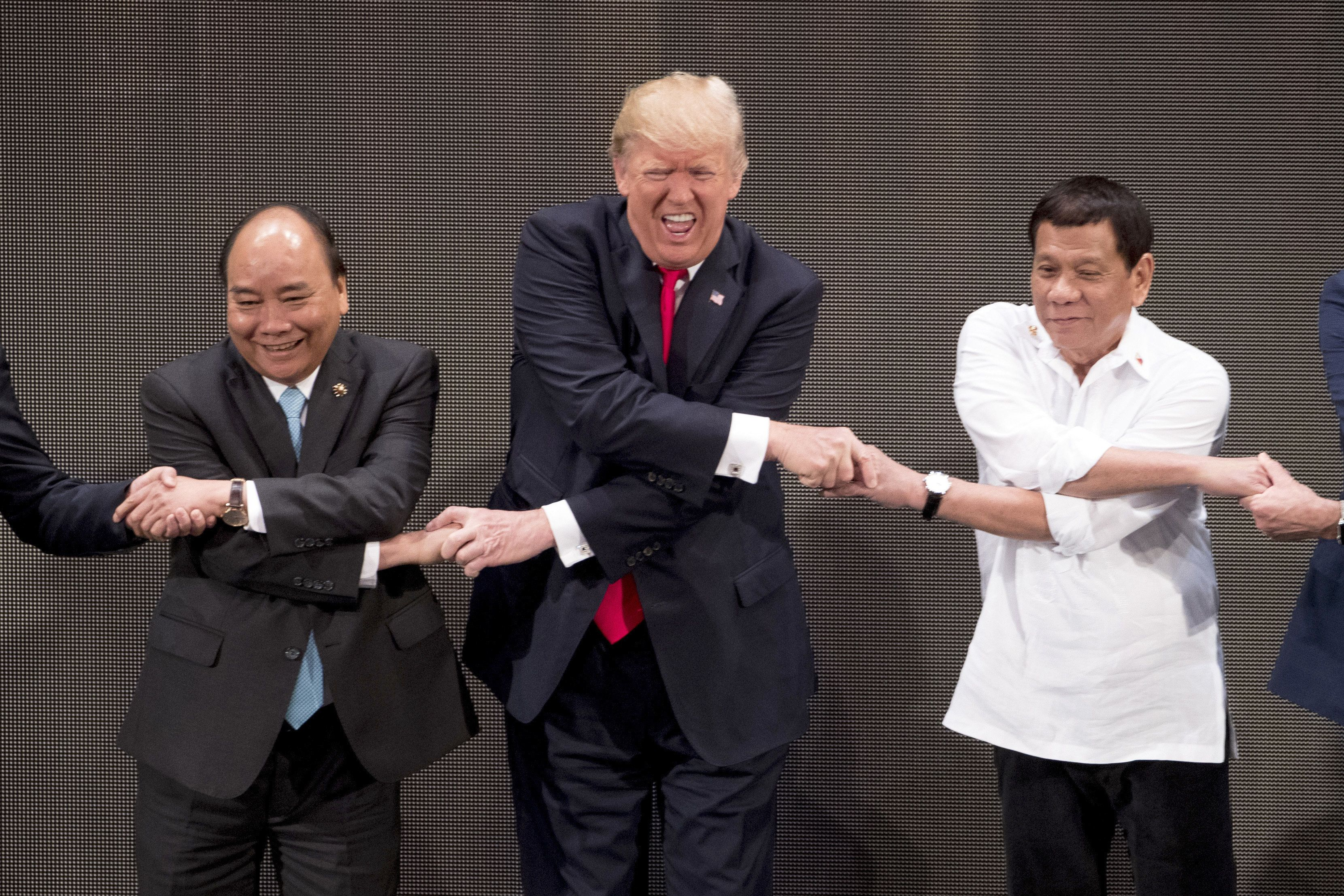 FILE  - In this Nov. 13, 2017, file photo, U.S. President Donald Trump, center, reacts as he does the ASEAN-way handshake' with Vietnamese Prime Minister Nguyen Xuan Phuc, left, and Philippine President Rodrigo Duterte on stage during the opening ceremony at the ASEAN Summit at the Cultural Center of the Philippines in Manila, Philippines. Trump has proven himself an unconventional leader time and time again in his first year in office. (AP Photo/Andrew Harnik, File)