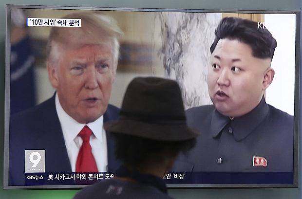 FILE - In this Aug. 10, 2017, file photo, a man watches a television screen showing U.S. President Donald Trump and North Korean leader Kim Jong Un during a news program at the Seoul Train Station in Seoul, South Korea. North Koreas state-run media say U.S. President Donald Trumps tweet about having a bigger nuclear button than Kim Jong Uns is the spasm of a lunatic.' (AP Photo/Ahn Young-joon, File)