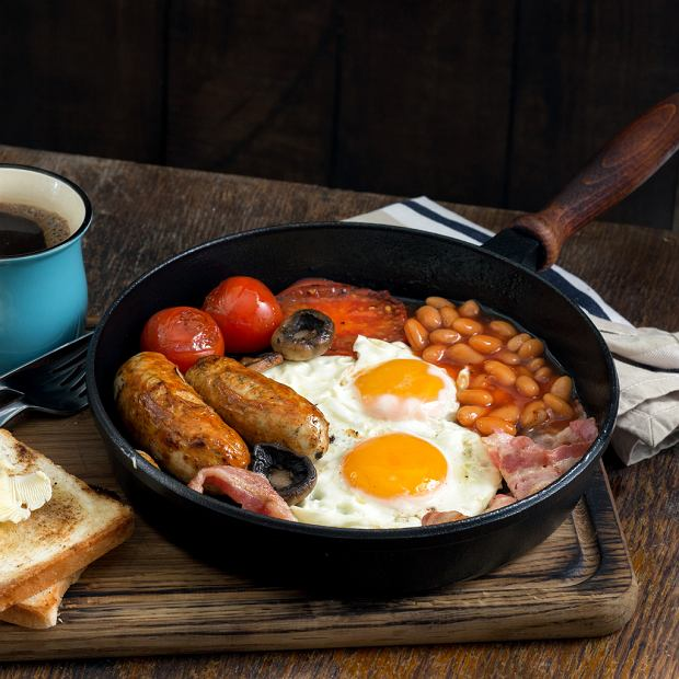 Full English breakfast on wooden table close-up