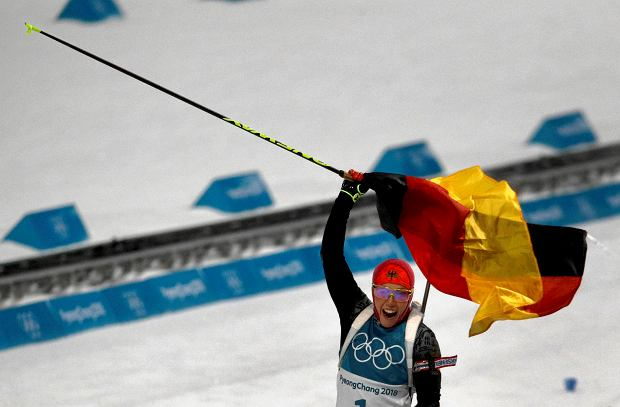 Laura Dahlmeier, of Germany, waves the German flag as she crosses the finish line to win the gold medal in the women