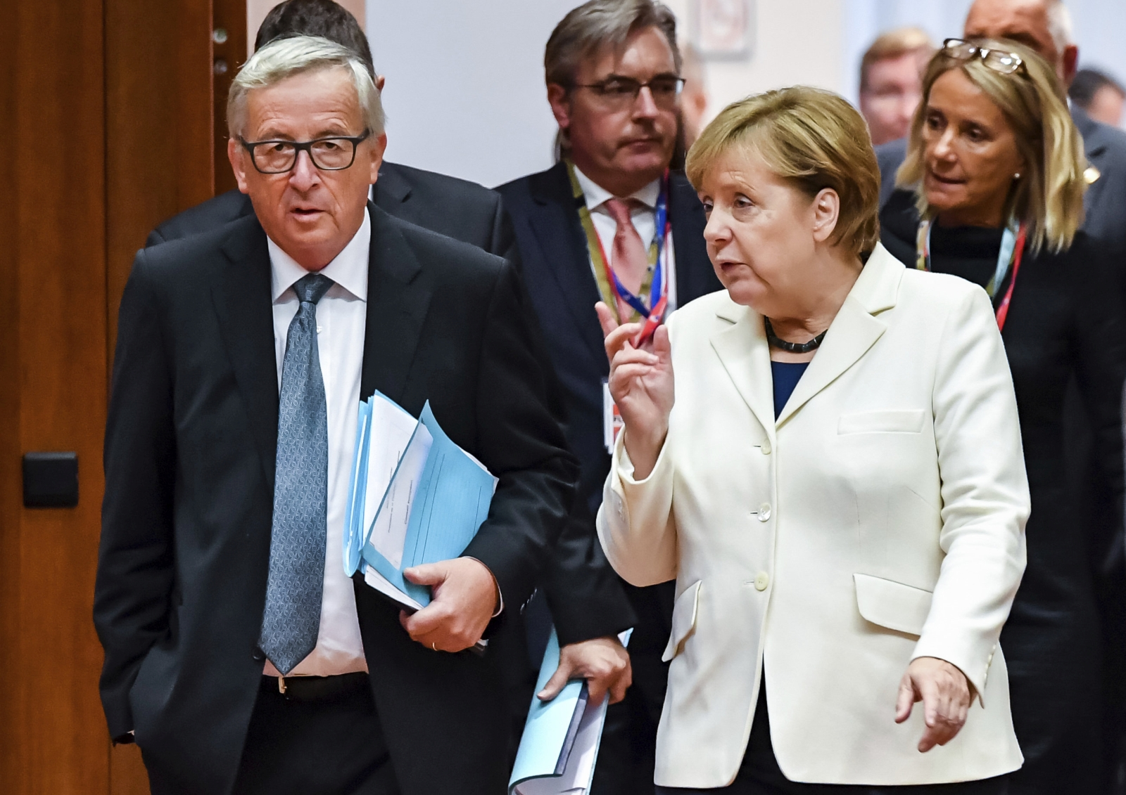 German Chancellor Angela Merkel, right, speaks with European Commission President Jean-Claude Juncker during a round table meeting at an EU summit in Brussels on Friday, Oct. 20, 2017. European Union leaders gathered Friday to weigh progress in negotiations on Britain's departure from their club as they look for new ways to speed up the painfully slow moving process. (AP Photo/Geert Vanden Wijngaert)