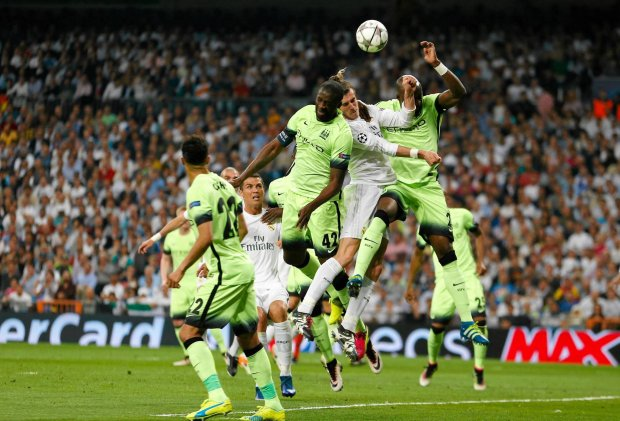 Real Madrid's Gareth Bale jumps for the ball with Manchester City's Fernandinho, right, and Manchester City's Yaya Toure during the Champions League semifinal second leg soccer match between Real Madrid and Manchester City at the Santiago Bernabeu stadium in Madrid, Wednesday May 4, 2016. (AP Photo/Francisco Seco) SLOWA KLUCZOWE: XCHAMPIONSLEAGUEX