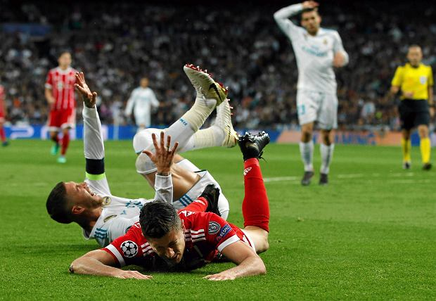 Bayern's Robert Lewandowski, bottom, and Real Madrid's Sergio Ramos sit on the pitch after making contact during the Champions League semifinal second leg soccer match between Real Madrid and FC Bayern Munich at the Santiago Bernabeu stadium in Madrid, Spain, Tuesday, May 1, 2018. (AP Photo/Paul White) SLOWA KLUCZOWE: XCHAMPIONSLEAGUEX