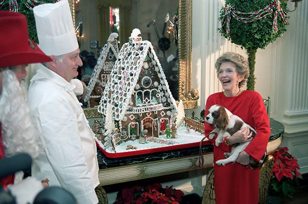 12/9/1985 Nancy Reagan holding her dog Rex attends a Christmas press preview with ginberbread house and Larry Hagman dressed up as Santa Claus