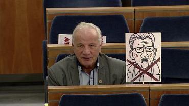 Senatorowie PO siedzą w ławach z karykaturami Piotrowicza