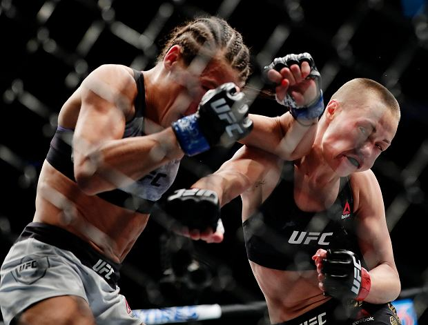 Rose Namajunas, right, punches Poland's Joanna Jedrzejczyk during the first round of a women's strawweight title bout at UFC 223, early Sunday, April 8, 2018, in New York. Namajunas won the bout (AP Photo/Frank Franklin II)
