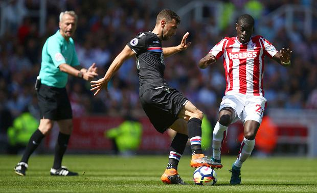 Crystal Palace's James McArthur, centre and Stoke City's Badou Ndiaye battle for the ball during the English Premier League soccer match between Stoke City and Crystal Palace, at the bet365 Stadium, in Stoke, England, Saturday May 5, 2018. (Dave Thompson/PA via AP) SLOWA KLUCZOWE: soccer;football