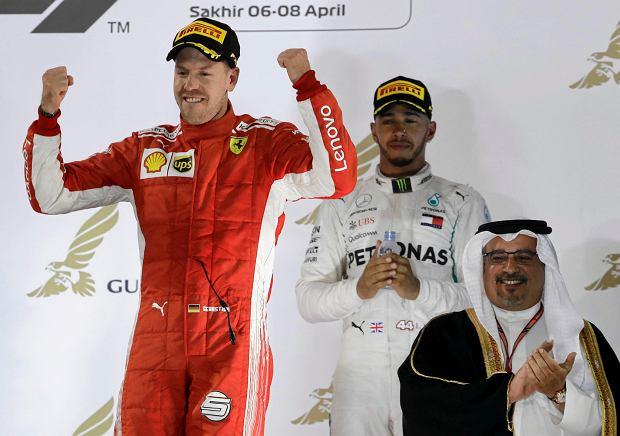 Ferrari driver Sebastian Vettel of Germany celebrates on the podium after winning the Bahrain Formula One Grand Prix, flanked by third place Mercedes driver Lewis Hamilton of Britain, at the Formula One Bahrain International Circuit in Sakhir, Bahrain, Sunday, April 8, 2018. (AP Photo/Luca Bruno) SLOWA KLUCZOWE: f1autoz18