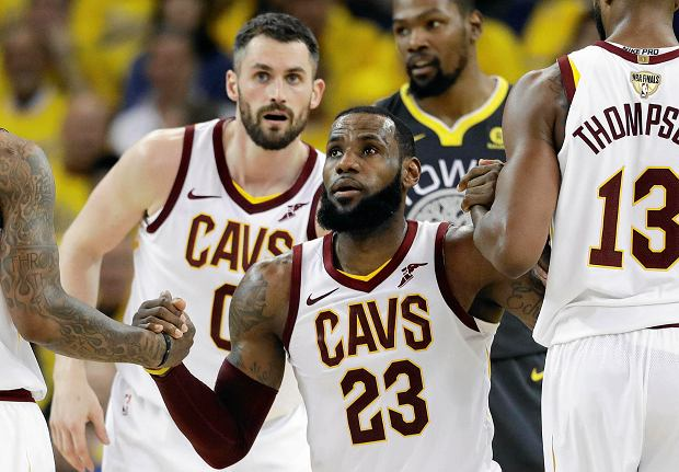 Cleveland Cavaliers forward LeBron James (23) is helped off the floor by teammates during the first half of Game 2 of basketball's NBA Finals against the Golden State Warriors in Oakland, Calif., Sunday, June 3, 2018. (AP Photo/Marcio Jose Sanchez)