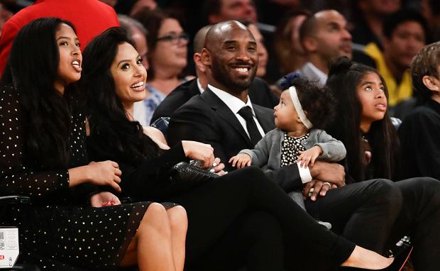 Former Los Angeles Laker Kobe Bryant watches a tribute video with his family during an NBA basketball game between the Los Angeles Lakers and the Golden State Warriors in Los Angeles, Monday, Dec. 18, 2017. The Lakers retired Bryant's No. 8 and No. 24 jersey during a halftime ceremony. (AP Photo/Chris Carlson)