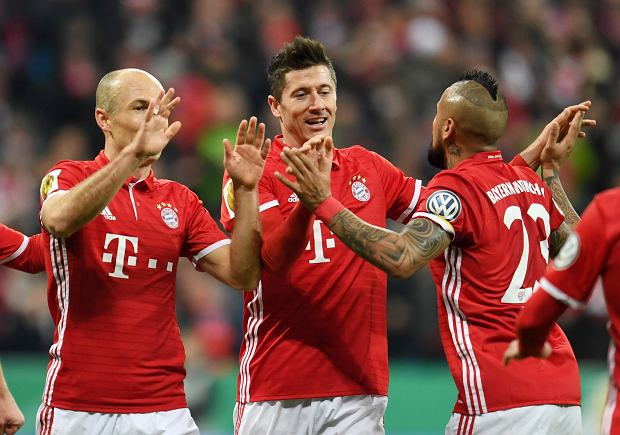 Bayern's Arjen Robben, Robert Lewandowski and Arturo Vidal from left, celebrate Lewandowski scoring, during the German soccer cup quarter final match between Bayern Munich and FC Schalke 04 in the Allianz Arena in Munich, Germany, Wednesday, March 1, 2017. (Tobias Hase/DPA via AP)