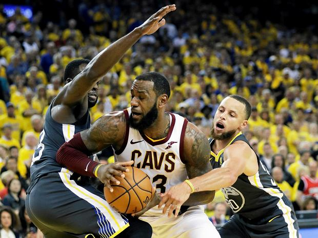Cleveland Cavaliers forward LeBron James, center, is defended by Golden State Warriors forward Draymond Green, left, and guard Stephen Curry during the second half of Game 2 of basketball's NBA Finals in Oakland, Calif., Sunday, June 3, 2018. (AP Photo/Marcio Jose Sanchez)