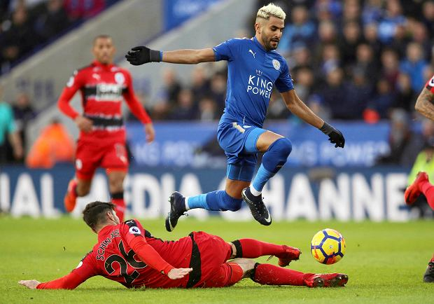 Leicester City's Riyad Mahrez, right, and Huddersfield Town's Christopher Schindler battle for the ball during their English Premier League soccer match at the King Power Stadium in Leicester, England, Monday Jan. 1, 2018. (Nigel French/PA via AP) SLOWA KLUCZOWE: soccer;football