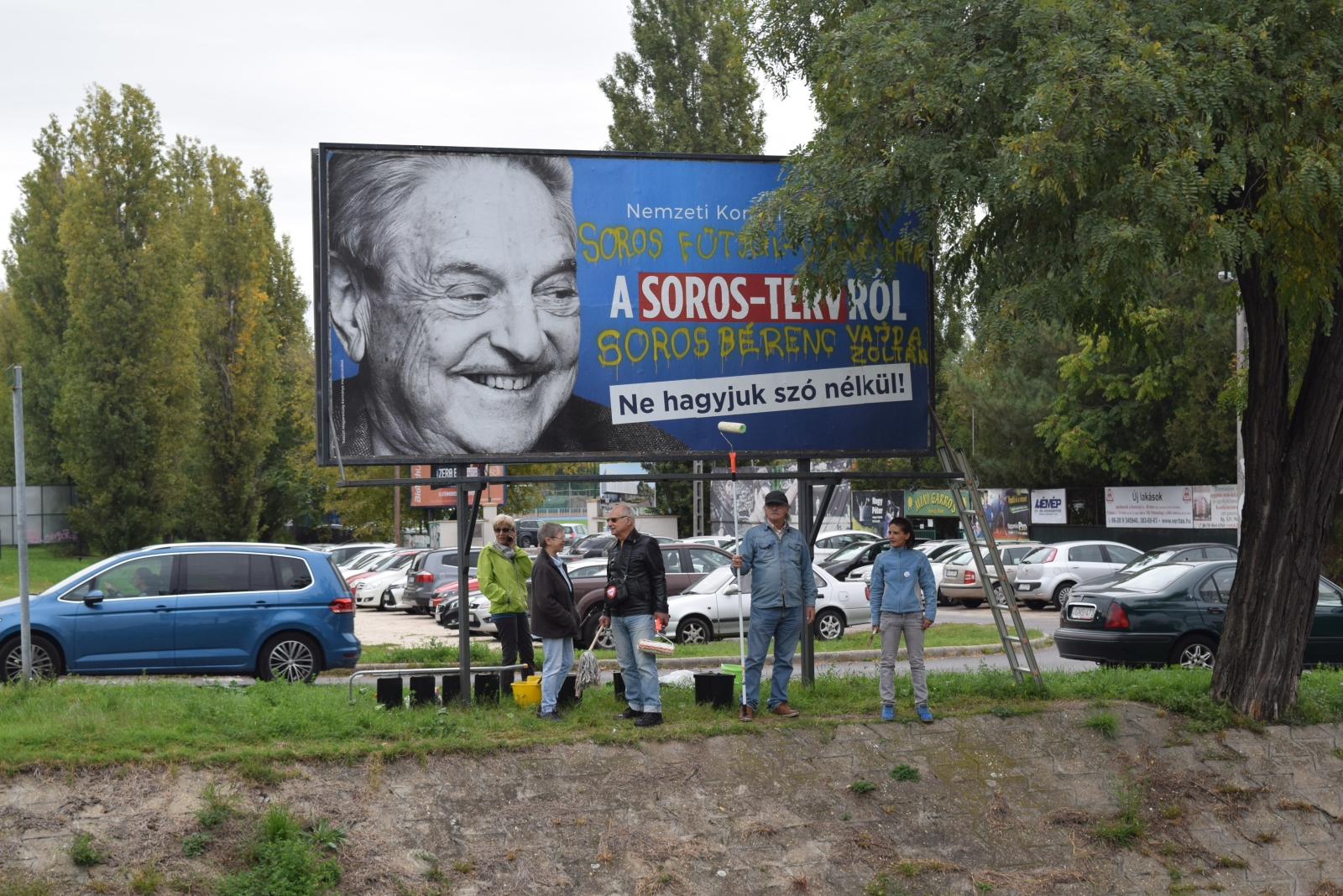 FILE - In this Oct. 5, 2017 file photo activists from the Egyutt (Together) opposition party stand in front of billboards of the government's campaign against George Soros and his support for migration in Budapest. Hungarian-American financier and philanthropist George Soros said oppression of the opposition by Prime Minister Viktor Orban's government is greater than when Hungary was under Soviet domination. (AP Photo/Pablo Gorondi, file)