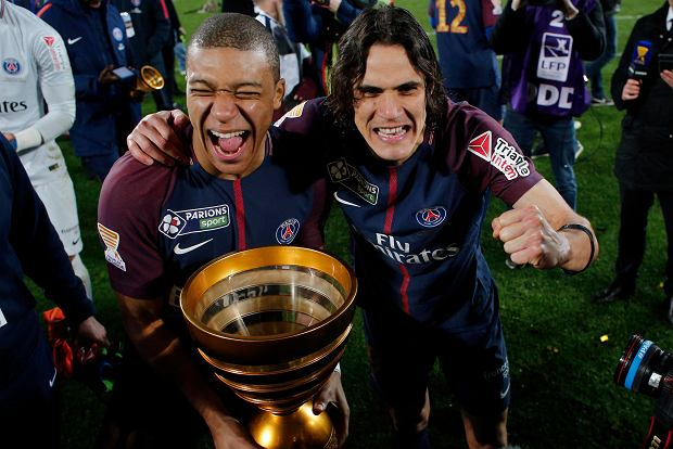 PSG's Edinson Cavani celebrates with Kylian Mbappe holding the trophy after winning the League Cup final soccer match against Monaco in Bordeaux, southwestern France, Saturday, March 31, 2018. (AP Photo/Thibault Camus)
