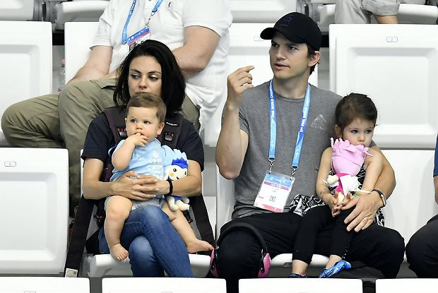 US actress Mila Kunis, left, and her husband US actor Ashton Kutcher, center, are seen with their children during the womens 3m synchro springboard final of the 17th FINA Swimming World Championships in Duna Arena in Budapest, Hungary, Monday, July 17, 2017. (Tibor Illyes/MTI via AP)