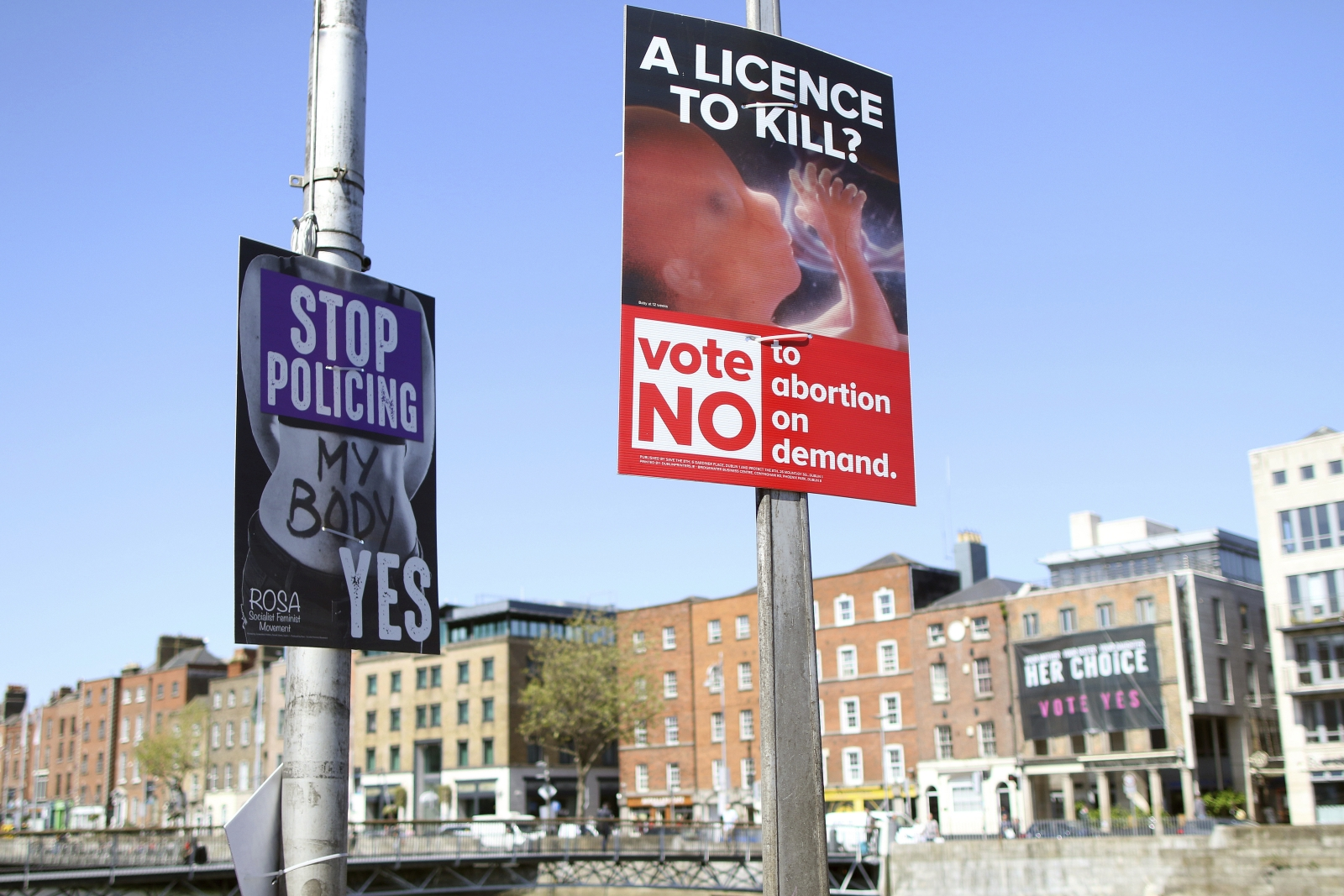 In this photo taken on May 17, 2018, pro and anti-abortion poster's on lampposts, in Dublin, Ireland. In homes and pubs, on leaflets and lampposts, debate rages in Ireland over whether to lift the country's decades-old ban on abortion. Pro-repeal banners declare: 'Her choice: vote yes.' Anti-abortion placards warn against a 'license to kill.' Online, the argument is just as charged _ and more shadowy _ as unregulated ads of uncertain origin battle to sway voters ahead of Friday's referendum, which could give Irish women the right to end their pregnancies for the first time. The emotive campaign took a twist this month when Facebook and Google look last-minute decisions to restrict or remove ads relating to the abortion vote. It is the latest response to global concern about social media's role in influencing political campaigns for the U.S. presidency and Brexit. (AP Photo/Peter Morrison)