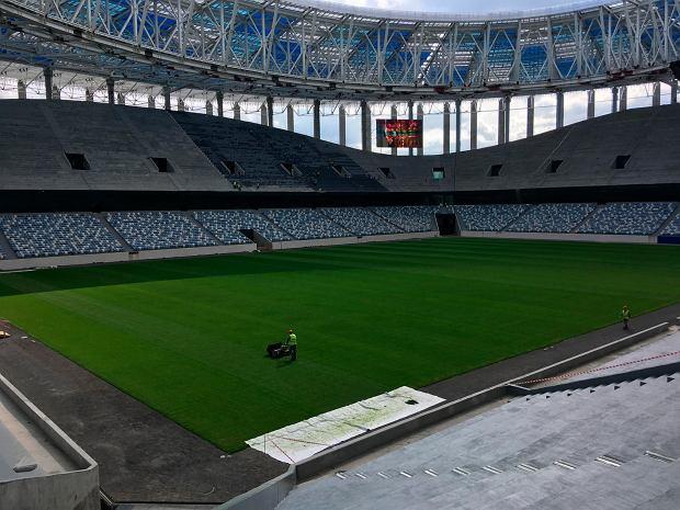 FILE - In this Saturday, Aug. 26, 2017 filer, laborers work at the construction site of the 2018 World Cup Nizhny Novgorod stadium, in Nizhny Novgorod, Russia. (AP Photo/James Ellingworth)