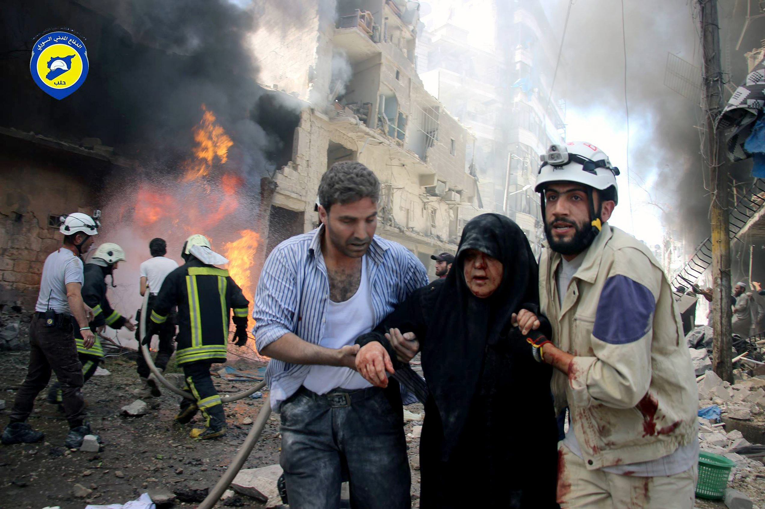 FILE - In this file photo taken on June 8, 2016 provided by the Syrian Civil Defense Directorate in Liberated Province of Aleppo, which has been authenticated based on its contents and other AP reporting, shows Syrian civil defense workers, right, helps an injured woman after warplanes attacked a street, in Aleppo, Syria. Residents trapped in rebel-controlled Aleppo are struggling to survive the crippling encirclement of their once thriving city. Bread, medication and fuel are running short. For the tens of thousands who chose to remain, the battle for Aleppo is a pivot point in the Syrian war. (Civil Defense Directorate in Liberated Province of Aleppo via AP, File)