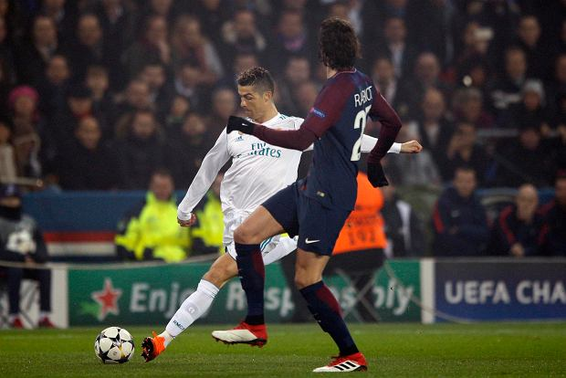 Real Madrid's Cristiano Ronaldo, left, makes an attempt to shot the ball as PSG's Adrien Rabiot tries to stop him during the round of 16, 2st leg Champions League soccer match between Paris Saint-Germain and Real Madrid at the Parc des Princes Stadium in Paris, Tuesday, March 6, 2018. (AP Photo/Francois Mori)