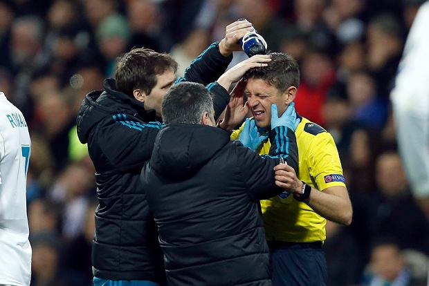 Referee Gianluca Rocchi of Italy is tended to by medics during a Champions League Round of 16 first leg soccer match between Real Madrid and Paris Saint Germain at the Santiago Bernabeu stadium in Madrid, Spain, Wednesday, Feb. 14, 2018. (AP Photo/Francisco Seco)