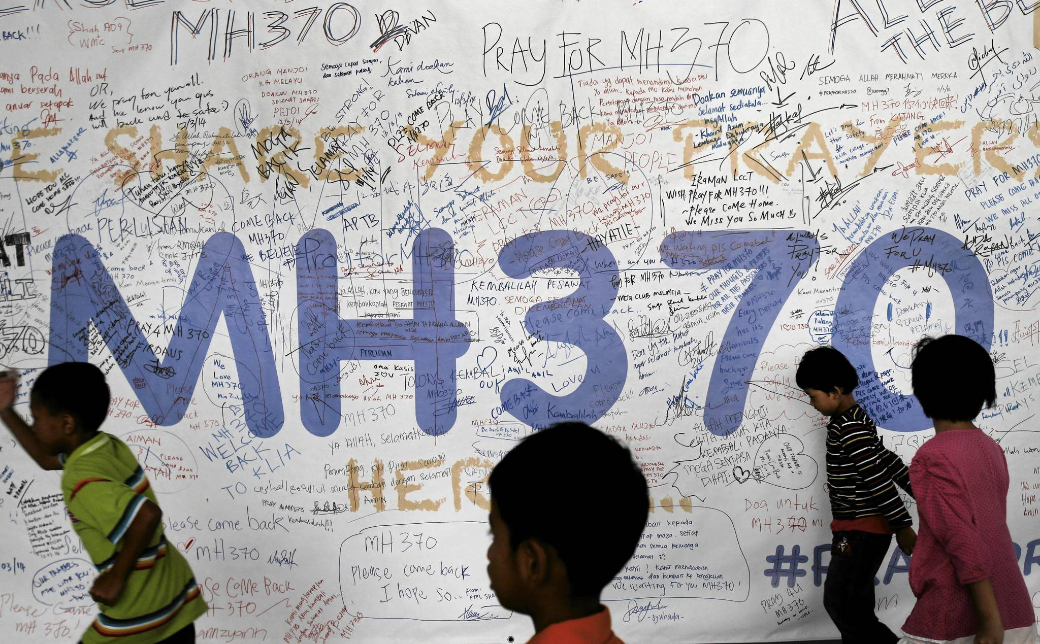 FILE - In this March 13, 2014, photo, children run past dedication messages left for passengers and others involved with the missing Malaysia Airlines jetliner MH370 on the walls of the Kuala Lumpur International Airport, in Sepang, Malaysia. Part of the mystery of what happened to a Malaysia Airlines plane that vanished last year may be solved with air safety investigators confident that debris found in the Indian Ocean is a wing part unique to the Boeing 777, the same model as the missing jet, a U.S. official said Wednesday, July 29, 2015. Air safety investigators - one of them a Boeing investigator -have identified the component that was found on the French island of Reunion in the western Indian Ocean as a