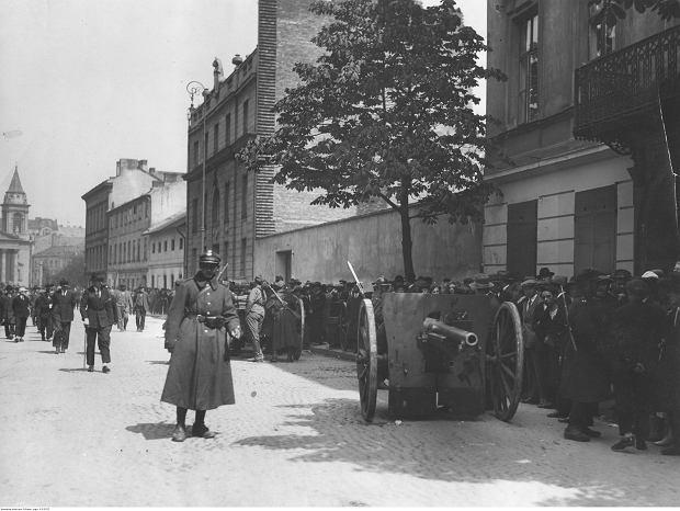Stanowisko artylerii na ulicy Mokotowskiej. Widoczna armata polowa 75 mm wz. 1897 Schneider oraz przyglądający się stanowisku tłumy ludzi.