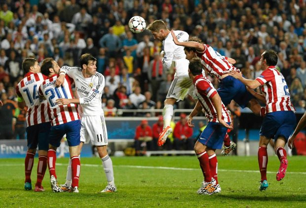 Real Madrid's Sergio Ramos, center, scores his side's first goal during the Champions League final soccer match against Atletico Madrid at the Luz Stadium in Lisbon, Portugal, Saturday, May 24, 2014. (AP Photo/Andres Kudacki) SLOWA KLUCZOWE: XCHAMPIONSLEAGUEX