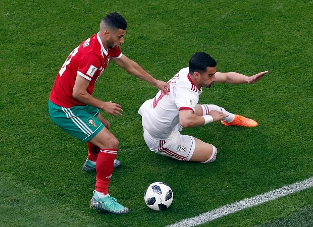 Morocco's Younes Belhanda, left, and Iran's Mehdi Torabi, right, challenge for the ball during the group B match between Morocco and Iran at the 2018 soccer World Cup in the St. Petersburg Stadium in St. Petersburg, Russia, Friday, June 15, 2018. (AP Photo/Thanassis Stavrakis) SLOWA KLUCZOWE: WC2018MAR;WC2018IRN