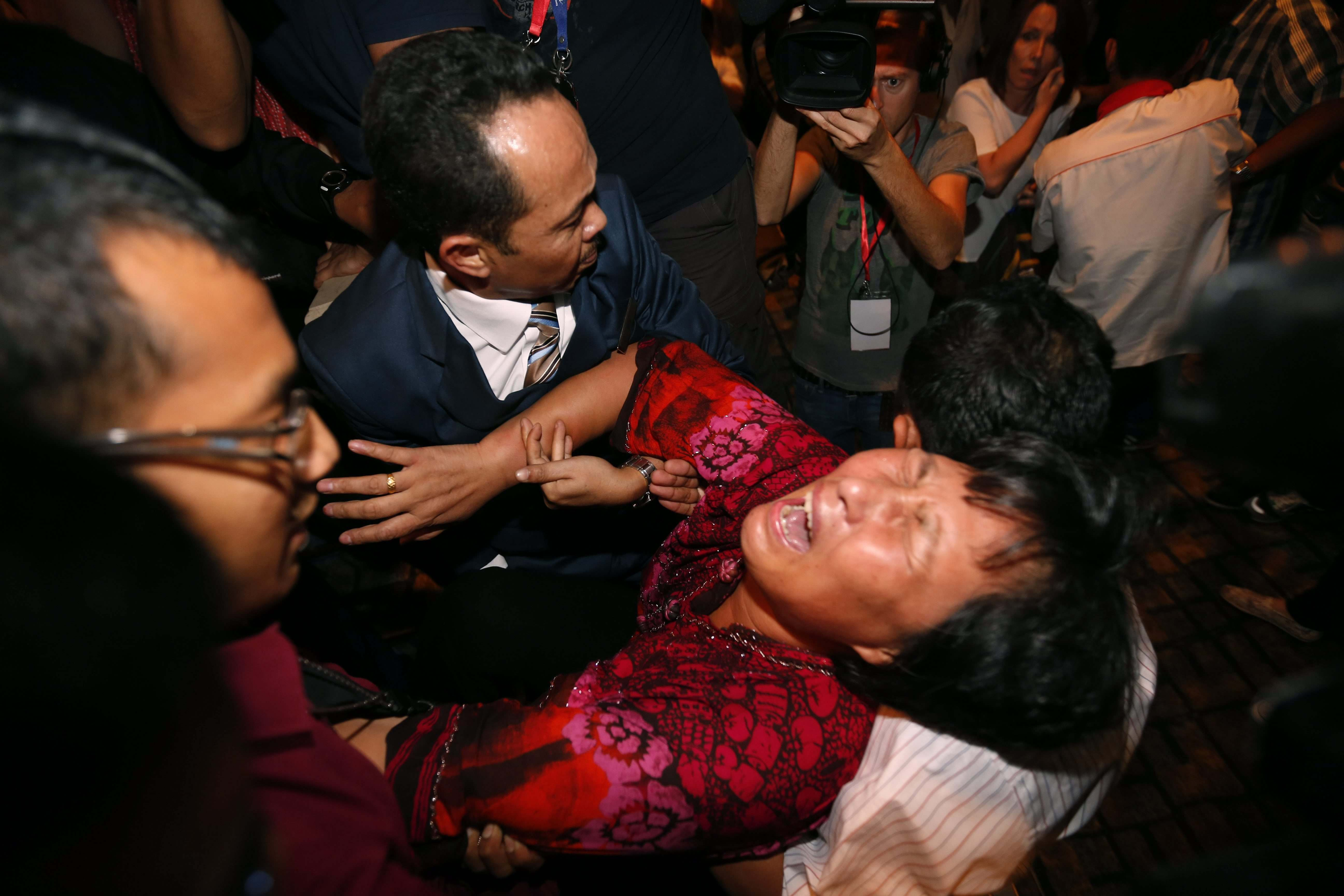 A Chinese relative of a passenger aboard a missing Malaysia Airlines plane is carried out by security officials as she protests before a press conference at a hotel in Sepang, Malaysia, Wednesday, March 19, 2014. New radar data from Thailand gave Malaysian investigators more potential clues Wednesday for how to retrace the course of the missing Malaysian airliner, while a massive multinational search unfolded in an area the size of Australia. (AP Photo/Vincent Thian)