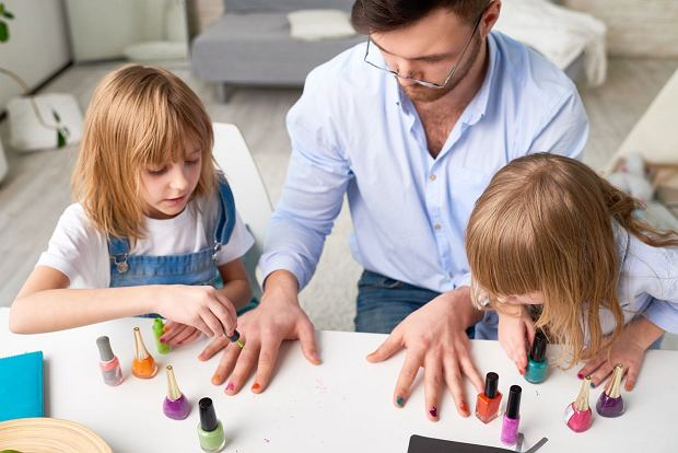 .Two sisters making fashion manicure for father