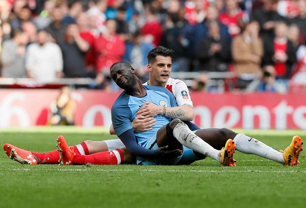 Arsenal's Granit Xhaka, right, embraces Manchester City's Yaya Toure during the English FA Cup semifinal soccer match between Arsenal and Manchester City at Wembley stadium in London, Sunday, April 23, 2017. (AP Photo/Kirsty Wigglesworth) SLOWA KLUCZOWE: XFACUPX