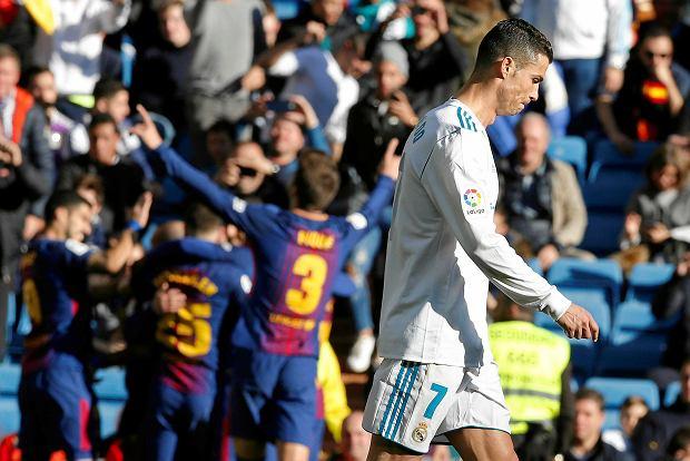 Real Madrid's Cristiano Ronaldo walks past as Barcelona players celebrate scoring their 3rd goal during a Spanish La Liga soccer match between Real Madrid and Barcelona at the Santiago Bernabeu stadium in Madrid, Spain, Saturday, Dec. 23, 2017. (AP Photo/Paul White) SLOWA KLUCZOWE: XLALIGAX