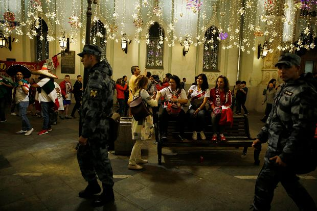 Russian security forces walk along pedestrian Nikolskaya Street, where fans from participating countries were gathered to celebrate and cheer on their teams on the eve of the 2018 soccer World Cup, in Moscow, Russia, Wednesday, June 13, 2018. (AP Photo/Rebecca Blackwell)