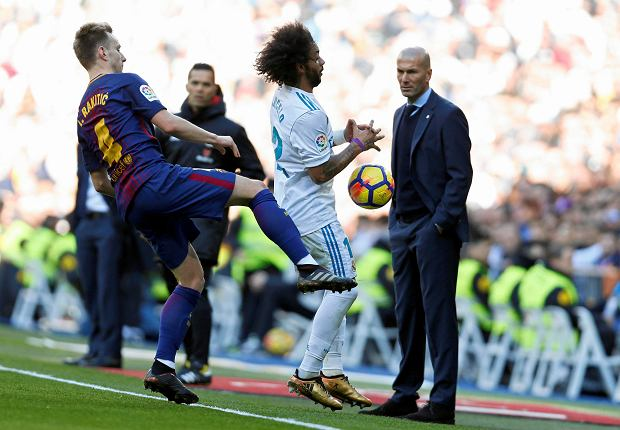 Real Madrid coach Zinedine Zidane, right, watches Barcelona's Ivan Rakitic, left, fight for the ball with Real Madrid's Marcelo during the Spanish La Liga soccer match between Real Madrid and Barcelona at the Santiago Bernabeu stadium in Madrid, Spain, Saturday, Dec. 23, 2017. (AP Photo/Francisco Seco) SLOWA KLUCZOWE: XLALIGAX