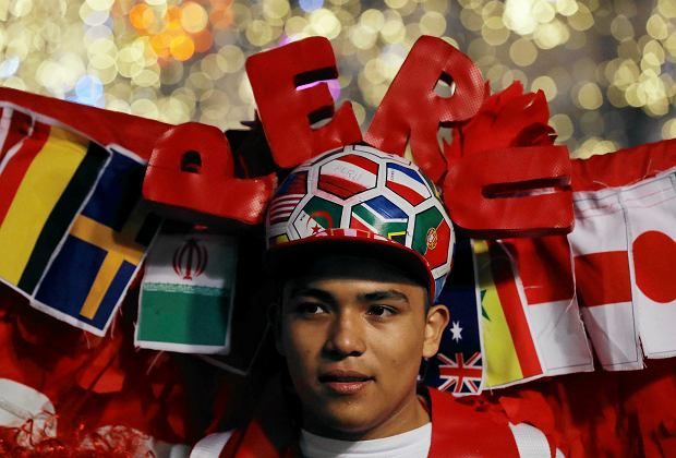 A Peru fan wears an elaborate costume featuring flags from participating countries, as soccer fans from around the world gathered to celebrate and cheer on their teams on the eve of the 2018 soccer World Cup, on Nikolskaya Street in Moscow, Russia, Wednesday, June 13, 2018. (AP Photo/Rebecca Blackwell)