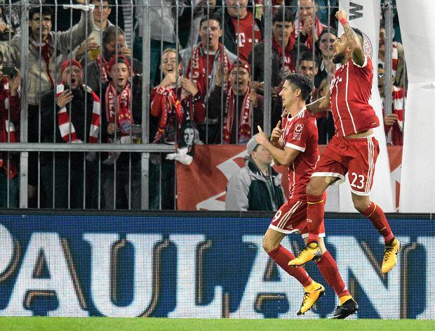 Bayern's Robert Lewandowski, left, celebrates after scoring his side's opening goal besides team mate Arturo Vidal during the German Soccer Bundesliga match between FC Bayern Munich and VfL Wolfsburg in Munich, Germany, Friday, Sept. 22, 2017. (Matthias Balk/dpa via AP)