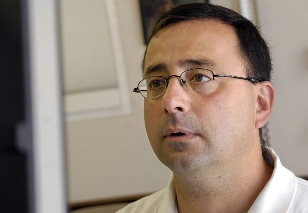 In a July 15, 2008 photo, Dr. Larry Nassar works on the computer after seeing a patient in Michigan. Multiple gymnasts, including a member of the 2000 U.S. women's Olympic team, said they were sexually abused by Nassar, a former longtime doctor for USA Gymnastics, court documents and interviews show. (Becky Shink/Lansing State Journal via AP)